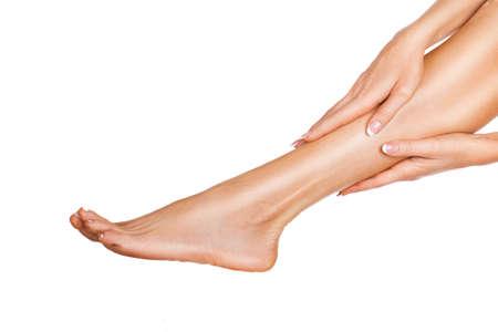 Mujer masajeando sus piernas aisladas sobre fondo blanco. Cerrar vista de piernas femeninas con piel y manos perfectas