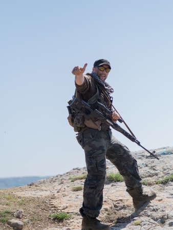 Scharfschütze, der mit Armen steht und zur Kamera schaut und Daumen hoch hält. Bewaffneter Konflikt.