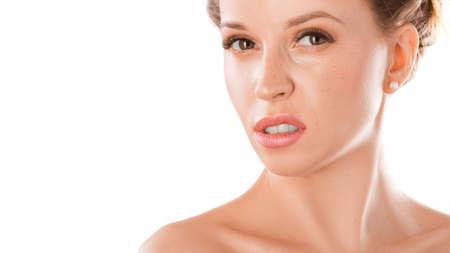 Mujer joven disgustada y con el ceño fruncido sobre un fondo blanco. Foto de archivo