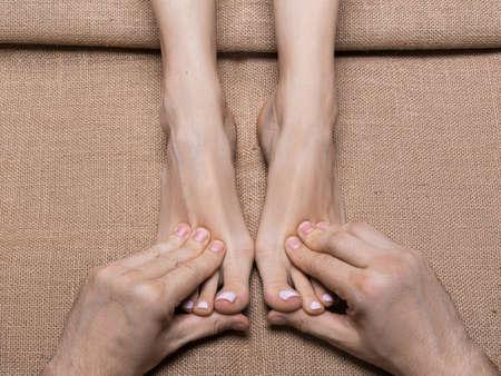 Man hands massaging womans feet on canvas. Spa salon.