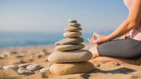 Woman practicing yoga on the beach. Balance ang relax. Zen. Selective focus