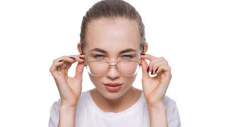 Young woman wearing glasses looking at camera with doubt and distrust. Problem with eyes, health care concept Imagens