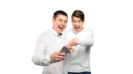 Two men looking at mobile phone and laugh, Isolated over white background 写真素材