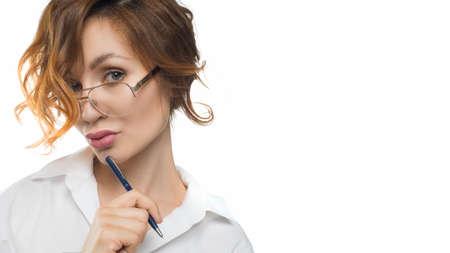 Pensive teacher woman in eyeglasses looks into the camera. Teacher. Business concept.