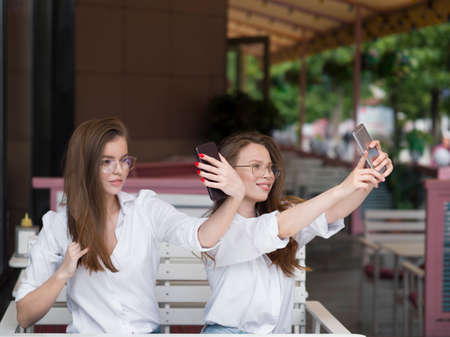 View of a two cute girls take a selfie while sitting in a summer cafe. Meeting and friendship concept. Social networks
