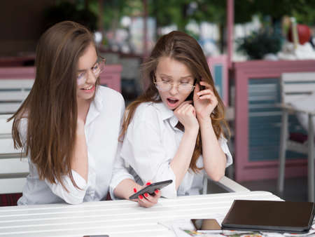 Two cheerful and beautiful girls are sitting together at a cafe and watching something on the phone