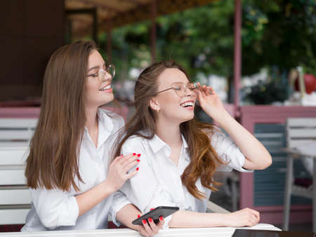 Two beautiful woman in eyeglasses sitting in summer cafe and looking by side.