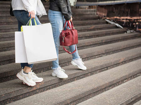 Two woman walk on the street with shopping bags