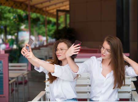 Two women makeing a selfie while sitting in a summer cafe. Meeting and friendship. Social networks concept.