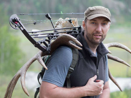 A hunter with a bow in the woods carries moose horns on his back and looking at camera.