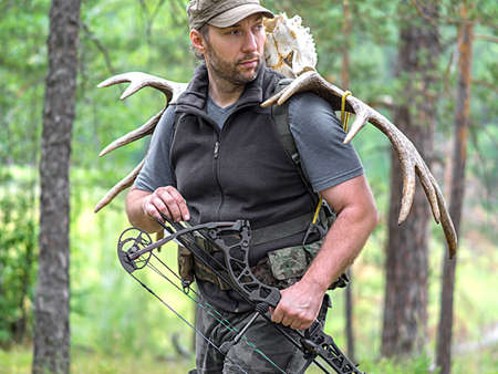 A hunter with a bow in the woods carries moose horns on his back and looking by side Stock Photo