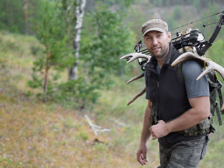 A hunter with a bow walks through the woods and carries elk or deer antlers on his back.