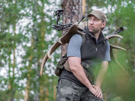 View of a hunter in the summer forest with a bow in the woods carries moose horns on his back