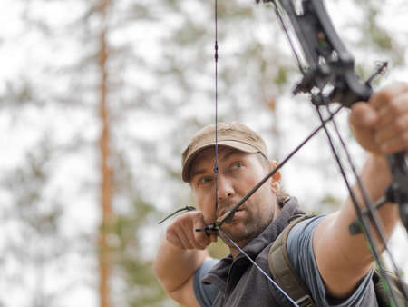 Man hunts in the forest with a bow. The hunter aims. 写真素材