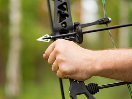 Bow hunting in the forest. Close-up hand holding a bow and an arrowhead. Stockfoto