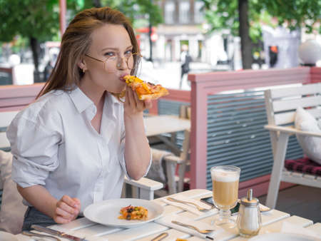 Outdoor portrait of a woman in eyeglasses eating pizza in summer cafe.