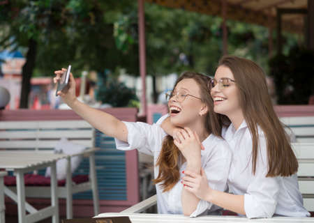 Nice meeting at a cafe. Summer holidays. Two girls make a selfie
