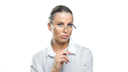 Pensive business woman in eyeglasses with a pen in her hand looks into the camera. Business concept.