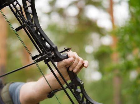 Man aims with a bow. Focus on the arrowhead. Bow hunting concept.