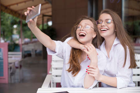 two happy girls making a selfie in summer cafe