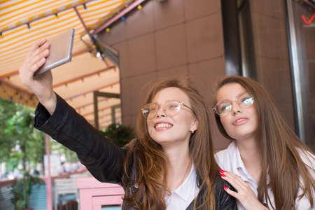 two girls in eyeglasses making a selfie in summer cafe