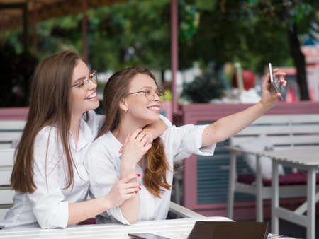 Two cute girls in eyeglasses making a selfie while sitting in a summer cafe. Social networks concept.