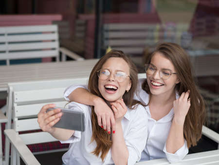 Nice meeting at a cafe. Summer holidays. Two girls make a selfie while sitting in summer cafe.