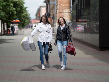 Young Women with Shopping Bags Walking City Street. Sale, Consumerism and People Concept