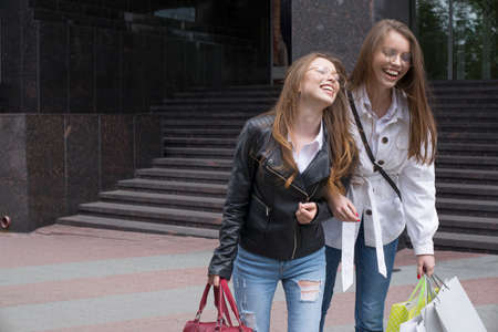 happy young women with shopping bags walking along city street