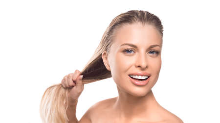 A woman with wet hair is smiling on a white background. Strength of hair concept