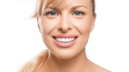 Close up portrait of a smiling woman on white background. Teeth whitening and stomatology concept