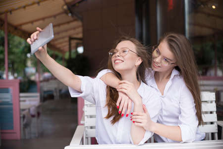 two girls making a selfie in summer cafe 写真素材