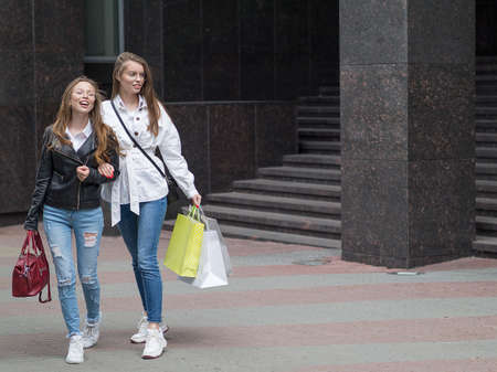 Beautiful stylish girl with bags walking down the street.