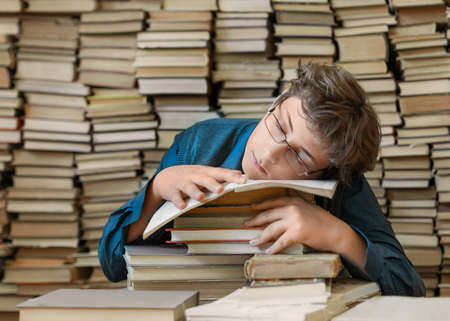 Sleeping boy as a pupil in the library with a big stack of books. Close up portrait.