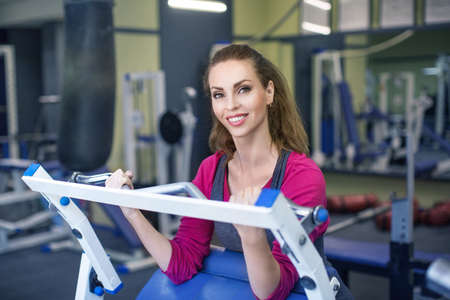 Close up photo of young woman flexing muscles on biceps machine in gym