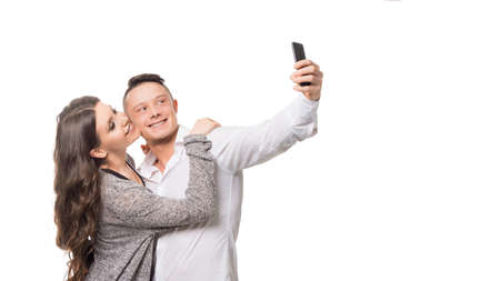Man and woman make a selfie over white background. Love and relationships concept. Фото со стока