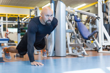 Brutal bearded man doing push ups exercise with one hand in fitness gym.