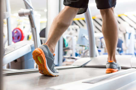 Male feet in sneakers running on the treadmill at the gym. Foto de archivo - 130113294