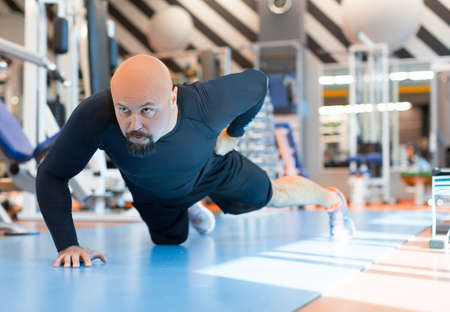 Brutal bearded man doing push ups exercise with one hand in fitness gym. Close up portrait Stock fotó