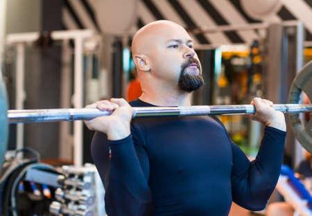 Brutaler Mann mittleren Alters, der eine Langhantel im Fitnessstudio hebt.