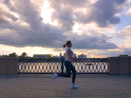 Young woman jogging by the River while listening to music. Foto de archivo - 130113548