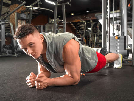 Man workout in fitness club. Portrait of caucasian guy making elbow plank exercise.