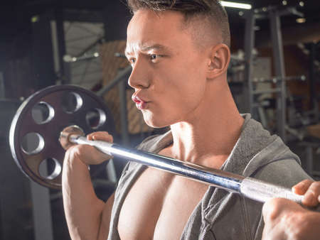 Side view of a young man man lifting a barbell in gym.