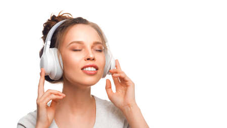 Attractive girl with closed eyes listening to the music via headphones on white background. Sound groove with closed eyes. Close up. Stok Fotoğraf