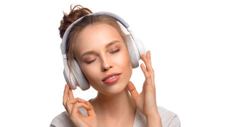 Attractive girl with closed eyes listening to the music via headphones on white background