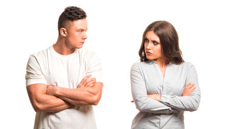 Unhappy couple holding arms crossed and looking each other isolated on white background. Family psychology concept.