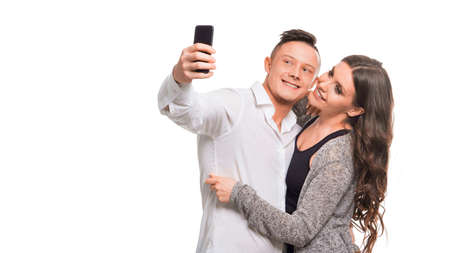 Young couple hugging and smiling while making selfie, standing over white isolated background. Stok Fotoğraf