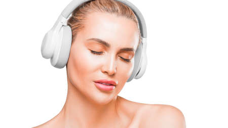 Portrait of a beautiful woman in white headphones listening to the music with closed eyes.