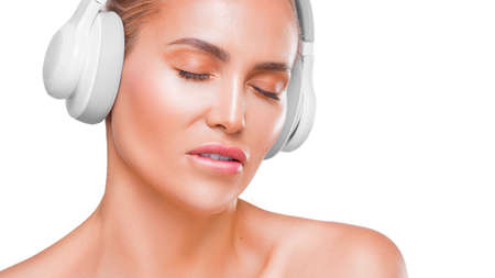 Portrait of a beautiful woman in white headphones enjoing music, bit her lip, with closed eyes. Stok Fotoğraf