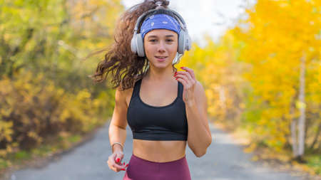 Woman jogging outdoor. Close up portrait - front view